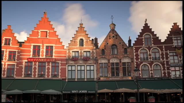 Clouds pass over the original buildings in Burg Square in Bruges, Belgium.
