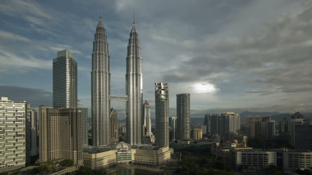 Clouds pass over the twin Petronas Towers and the Kuala Lumpur City Center.