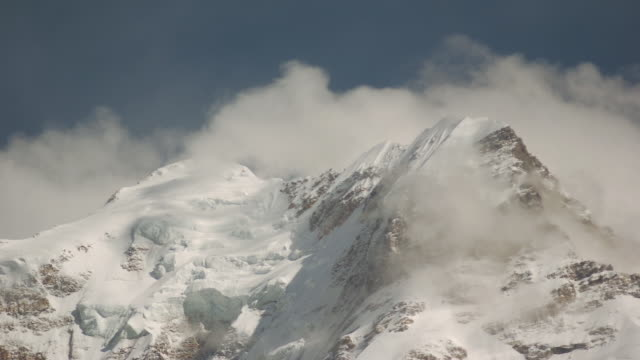 clouds pass over tolma peak. - snowcapped mountain stock videos and b-roll footage