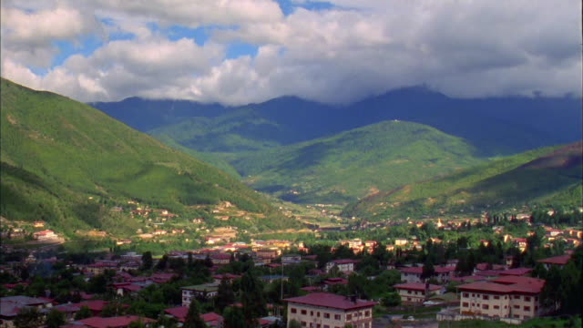Clouds pass over village in valley of Himalayas, Paro Available in HD.