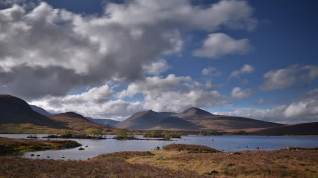 vídeos y material grabado en eventos de stock de clouds pass overhead and are reflected in the water of rannoch moor in the highlands of scotland - erial