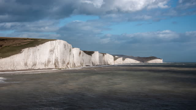 clouds pass rapidly overhead as rough seas travelled towards the iconic white cliffs of the seven sisters on the south coast of england dappled sunlight travels across the cliff face - サウスダウンズ点の映像素材/bロール
