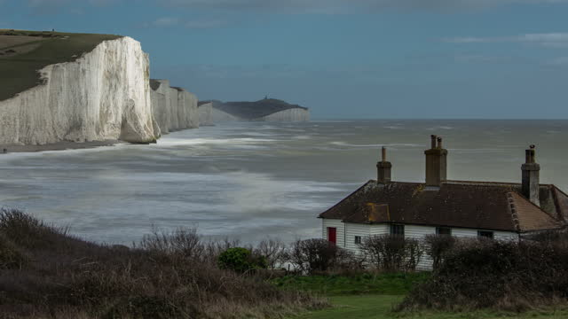 clouds pass rapidly overhead as rough seas travelled towards the iconic white cliffs of the seven sisters on the south coast of england dappled sunlight travels across the cliff face in the foreground a traditional cottage perches on the cliff edge - サウスダウンズ点の映像素材/bロール