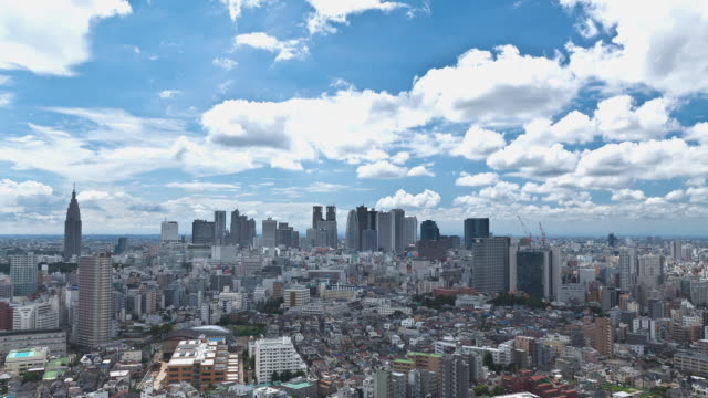 WS T/L Clouds passing over Shinjuku business and entertainment area of Tokyo during summer afternoon / Tokyo, Japan