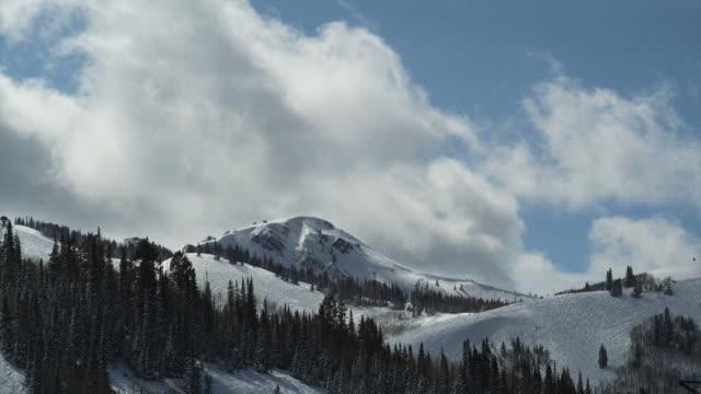 vídeos de stock, filmes e b-roll de clouds passing over snow-capped mountains - park city utah