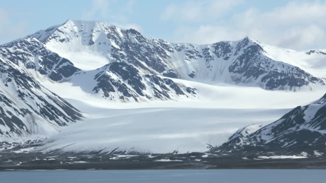 TL Clouds passing over snowy mountaintops near a lake / Svalbard, Norway