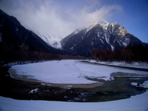 t/l clouds passing over snowy valley with river in foreground, kamikochi, japan - nagano prefecture stock videos & royalty-free footage