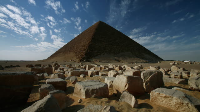 T/L, WS, clouds passing over the Red Pyramid with rocky limestone blocks in foreground / Dahshur, Nile Valley, Egypt