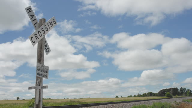 vídeos de stock, filmes e b-roll de ws tl clouds passing over train tracks and railroad crossing sign with field in background/ north dakota - passagem de nível