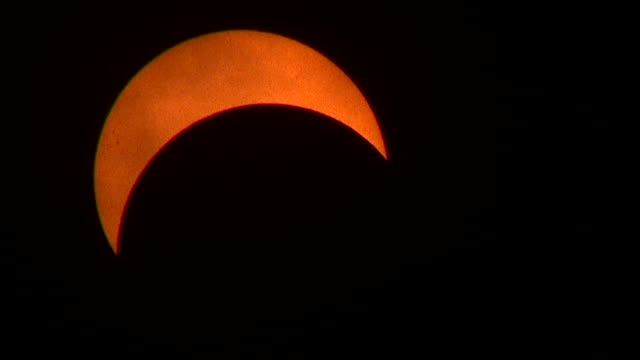 vídeos y material grabado en eventos de stock de clouds periodically race past the sun at the peak of 71% totality in the new york city metro during the august 21st 2017 great american eclipse a few... - mancha solar