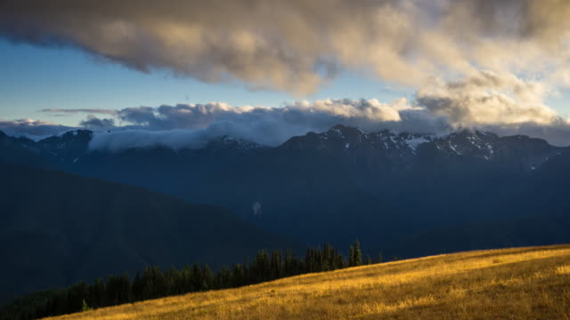 clouds pouring over mountains in olympic national park - day to night time lapse - olympic national park stock videos and b-roll footage