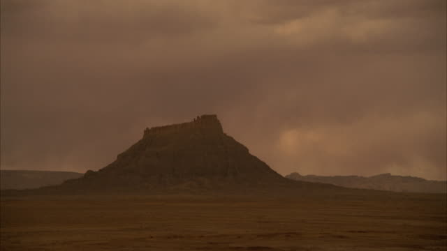 clouds race above a desert butte. - butte rocky outcrop stock videos and b-roll footage