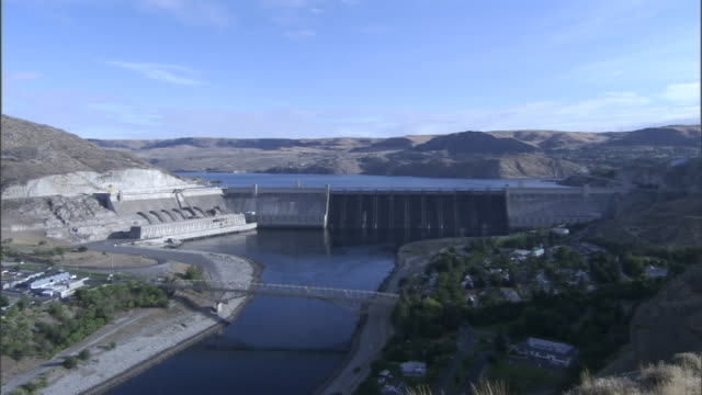 clouds race above a large dam and reservoir. - reservoir stock videos & royalty-free footage
