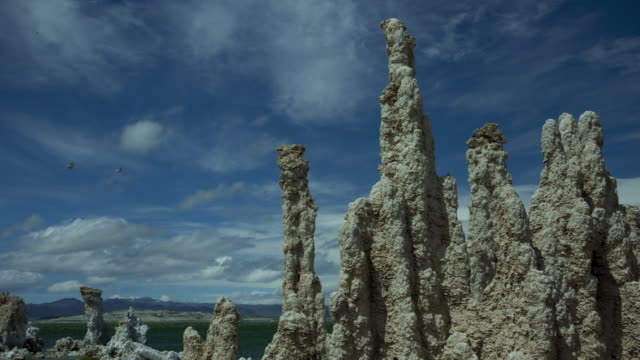 vídeos de stock e filmes b-roll de clouds race above pinnacle-like rock formations. - chaminé de fada
