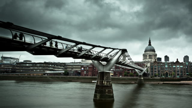 Clouds race above the Millennium Bridge and St. Paul's Cathedral in London.
