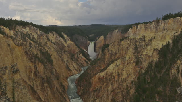 clouds race in time lapse over the cascading lower yellowstone falls in wyoming's grand canyon of the yellowstone. - lower yellowstone falls stock videos & royalty-free footage