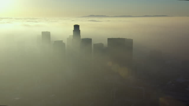 Clouds reach to the horizon as the skyscrapers of downtown Los Angeles emerge from the city's smog.