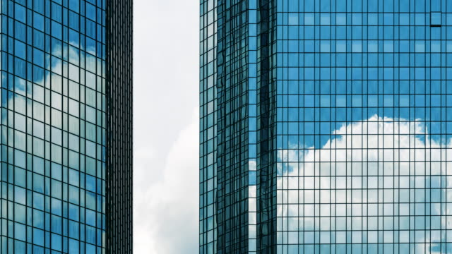 clouds reflected in mirrored office windows - gebäudefront stock-videos und b-roll-filmmaterial