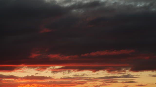 clouds reflecting the warm red glow of the sun at dusk - weather stock videos & royalty-free footage