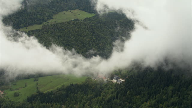 LOW AERIAL WS ZI Clouds revealing landscape and part of Grande Chartreuse Carthusian monastery in Chartreuse Mountains / Saint-Pierre-de-Chartreuse, Isere, France