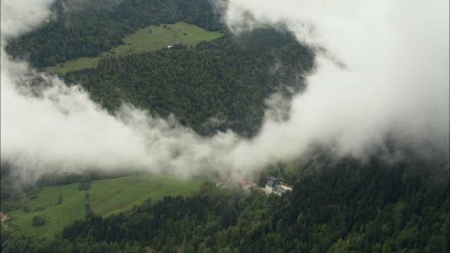 vidéos et rushes de low aerial ws zi clouds revealing landscape and part of grande chartreuse carthusian monastery in chartreuse mountains / saint-pierre-de-chartreuse, isere, france - vallée