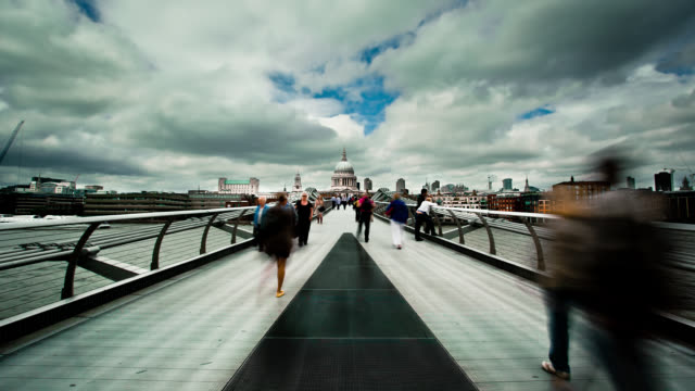 clouds roll above pedestrians who race along the millennium bridge in london. - london millennium footbridge stock videos & royalty-free footage