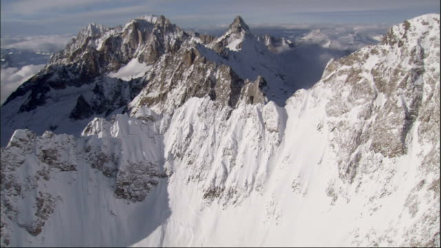 Clouds roll over snow covered mountains in the French Alps Available in HD.