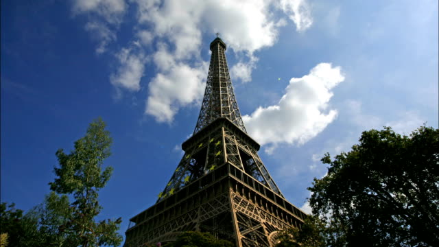 clouds roll over the eiffel tower in paris, france. - eiffel tower paris stock videos & royalty-free footage