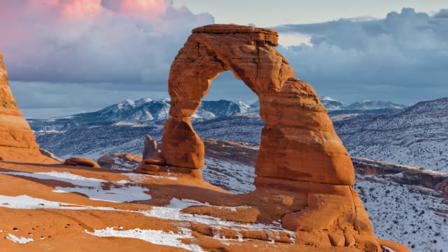 T/L  Clouds rolling behind Delicate Arch and La Sal Mountains at sunset in winter / Arches National Park, Utah, USA