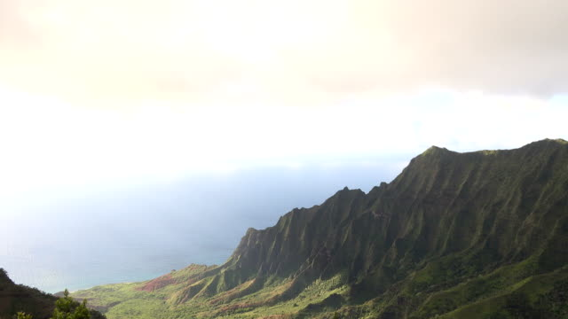 clouds rolling over kauai island with clear ocean beyond - butte rocky outcrop stock videos & royalty-free footage