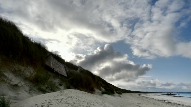 clouds rolling over the dunes - オオハマガヤ属点の映像素材/bロール