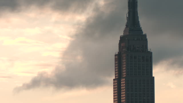 clouds rush by the tower of the empire state building on a gloomy cloudy morning - empire state building stock-videos und b-roll-filmmaterial