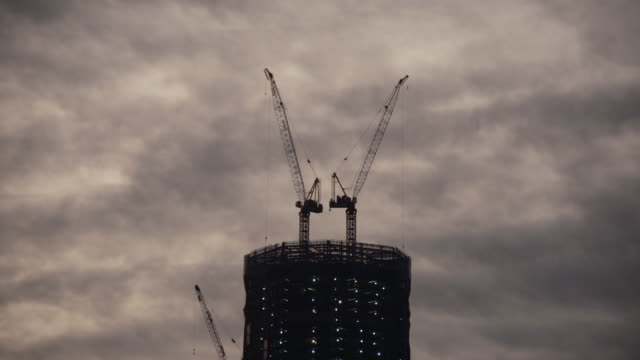 clouds rush past the construction tower of the new freedom tower in by the world trade center site - one world trade center stock-videos und b-roll-filmmaterial