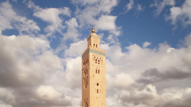 clouds sail over the koutoubia mosque in marrakech, morocco. - moschee stock-videos und b-roll-filmmaterial