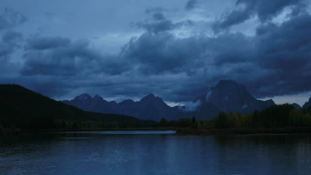 clouds scud over grand teton as day breaks. - mt moran stock videos & royalty-free footage