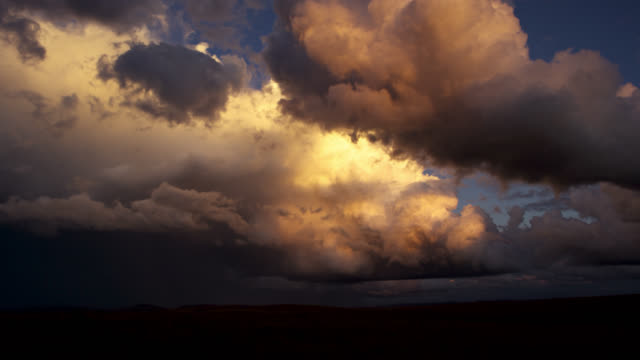 Clouds scud over hills of cerrado grassland at sunset.