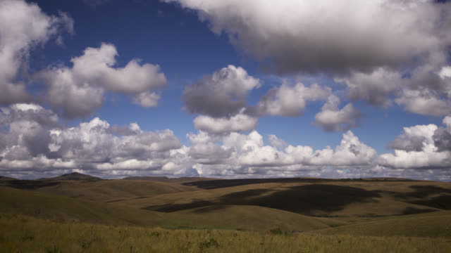 Clouds scud over hills of cerrado grassland.