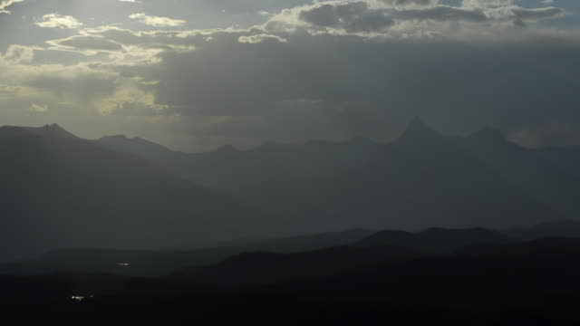 clouds scud over mountains as night falls. - mountain range stock videos & royalty-free footage
