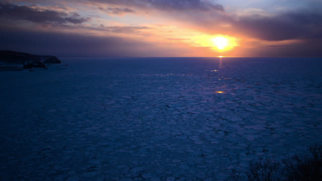 clouds scud over sea ice at sunset. - frozen stock videos & royalty-free footage