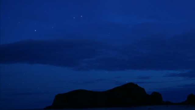 Clouds scud over silhouetted rocks as night falls, stars wheel over coast.