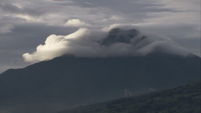 clouds shroud the summit of a volcano in the virunga mountains. available in hd. - parc national des volcans rwanda stock videos and b-roll footage
