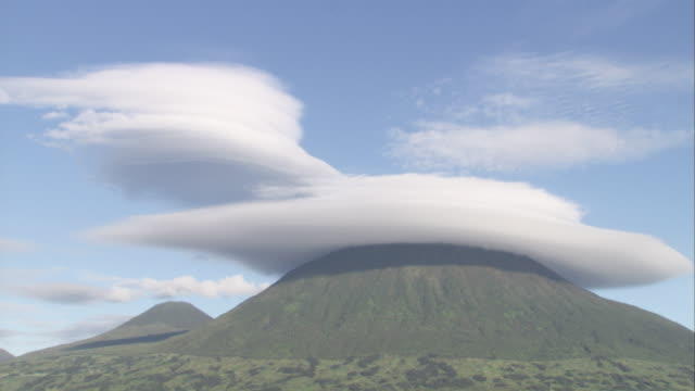 Clouds shrouds Virunga Mountain peak. Available in HD.