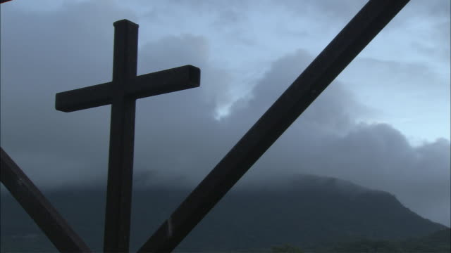 ms la clouds slowly moving behind tall cemetery gate with cross in middle, yarrabah mission, queensland, australia - kreuz religiöser gegenstand stock-videos und b-roll-filmmaterial