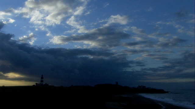 Clouds streak the sky above the village of Happisburgh and its lighthouse. Available in HD.