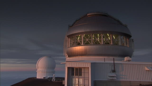 clouds streak the sky behind telescopes at the w. m. keck observatory on hawaii's big island. - osservatorio video stock e b–roll