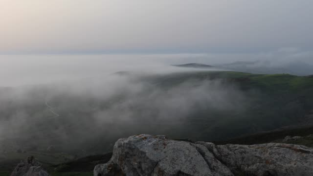Clouds stream along distant hillcrests