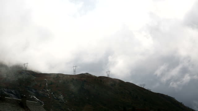 clouds stream past mountains and power pylons - overhead projector stock videos & royalty-free footage
