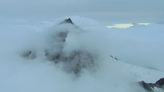 Clouds Surround Snow Covered Peak