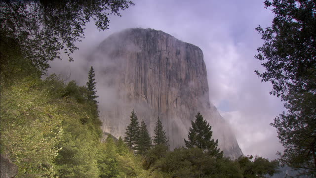 clouds surround the el capitan cliff in the yosemite national park. - エルキャピタン点の映像素材/bロール