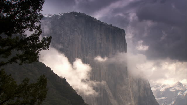 clouds surround the el capitan cliff in the yosemite national park. - yosemite nationalpark stock-videos und b-roll-filmmaterial